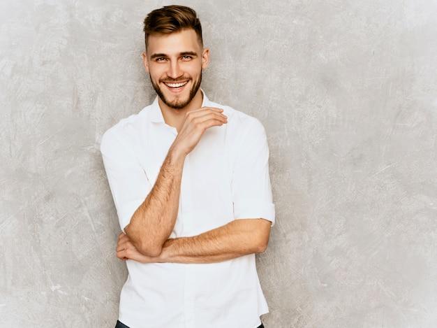 カジュアルな夏の白いシャツを着てハンサムな笑みを浮かべて流行に敏感なビジネスマンモデルの肖像画。 無料写真