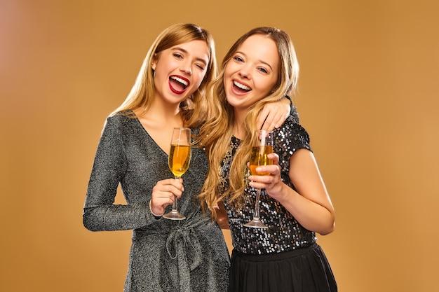 金色の壁にシャンパングラスとスタイリッシュな魅力的なドレスで幸せな笑顔の女性 無料写真
