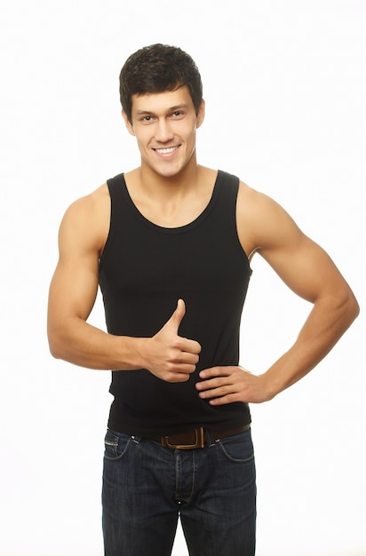成功した筋肉の若い男が親指を現して笑顔 無料写真
