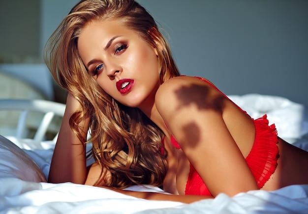 朝ベッドに赤いランジェリーを着ている女性モデル 無料写真