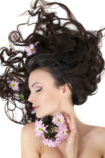 白で隔離される彼女の髪の明るいメイクで明るい花で横になっている非常に美しい女の子 無料写真