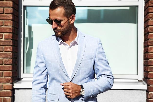 通りの背景にポーズをとってエレガントな青いスーツに身を包んだセクシーなハンサムなファッションビジネスマンモデルの肖像画。メトロセクシャル 無料写真