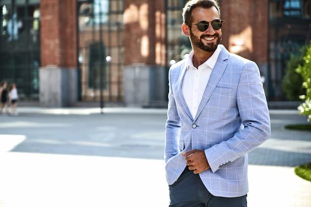 Портрет сексуальной красивой модели бизнесмена модели одел в изящном синем костюме, позирующем на уличном фоне. метросексуал Бесплатные Фотографии