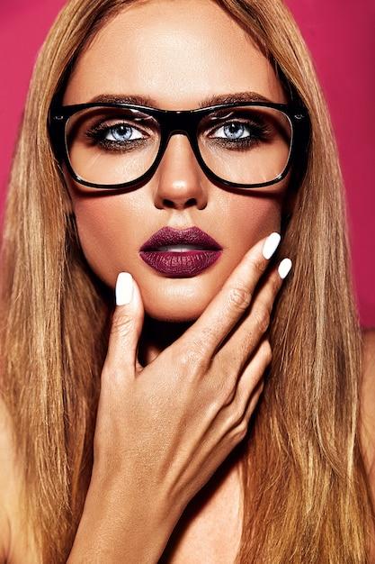 Чувственный гламур портрет красивой блондинки модели со свежим ежедневным макияжем с фиолетовым цветом губ и чистой здоровой кожей в очках на розовом фоне Бесплатные Фотографии