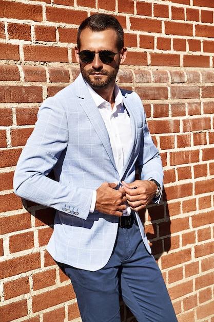Портрет сексуальной красивой модели бизнесмена модели одел в изящном синем костюме, позирующем около кирпичной стены на фоне улицы. метросексуал Бесплатные Фотографии