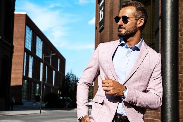 通りの背景にポーズをとってエレガントなスーツに身を包んだセクシーなハンサムなファッションビジネスマンモデルの肖像画。メトロセクシャル 無料写真