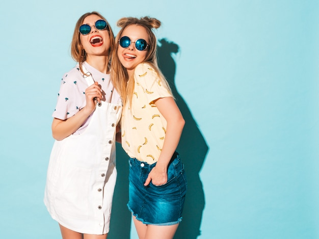 Две молодые красивые улыбающиеся белокурые хипстерские девочки в модной летней красочной футболке одеваются. Бесплатные Фотографии