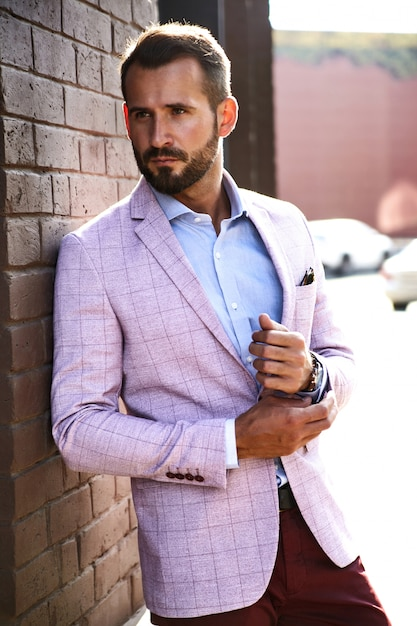 Портрет сексуальный красивый модный бизнесмен модель, одетый в элегантный костюм, позирует возле кирпичной стены на фоне улицы. метросексуал Бесплатные Фотографии