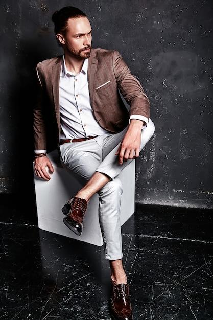 Портрет красивый модный стильный битник бизнесмен модель, одетый в элегантный коричневый костюм, сидя возле Бесплатные Фотографии