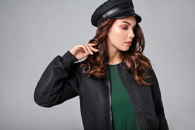 Портрет молодой стильной смеющейся модели в черной повседневной летней одежде в кепке с натуральным макияжем на сером Бесплатные Фотографии