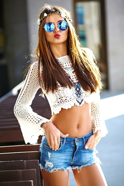 Смешные стильные сексуальные улыбающиеся красивые молодые хиппи женщина модель в летних белых одеждах битник позирует на улице Бесплатные Фотографии