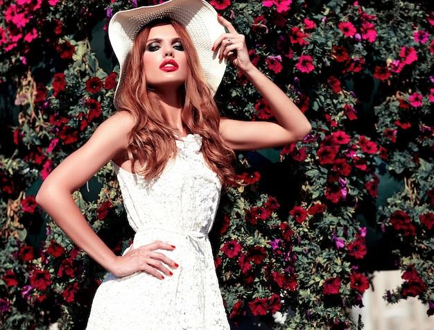 Портрет красоты очарования красивой чувственной кавказской модели молодой женщины с вечерней косметикой в белом летнем платье, позирующем на уличном фоне около цветочного фона Бесплатные Фотографии