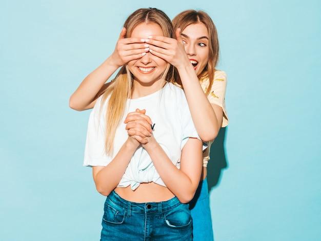 彼女の女性の親友を驚くべき女の子。彼女の目を覆い、後ろから抱き締めるモデル。 無料写真