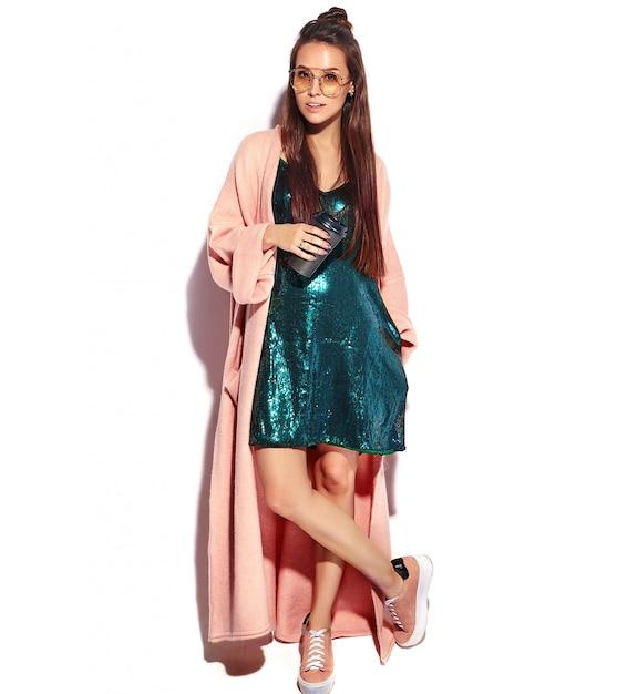 スタイリッシュなピンクのオーバーコートで美しい笑顔ヒップスターブルネットの女性モデル。コーヒーを飲む、全長 無料写真