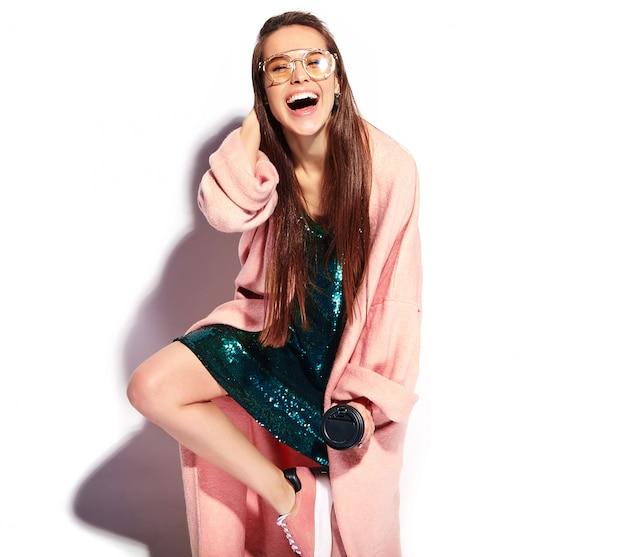 スタイリッシュなピンクのオーバーコートで美しい笑顔ヒップスターブルネットの女性モデル。コーヒーを飲んでいる 無料写真