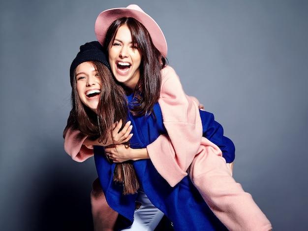 Портрет моды двух улыбающихся моделей брюнетки в летнем повседневном хипстерском пальто, излагающем. девушки держат друг друга на спине Бесплатные Фотографии