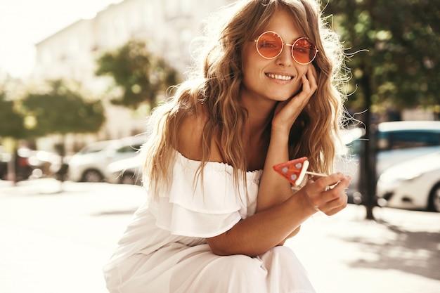 通りの背景の上に座ってスイカキャンディーと夏の流行に敏感な白いドレス服に化粧なしで美しいかわいい金髪ティーンエイジャーモデルの肖像 無料写真