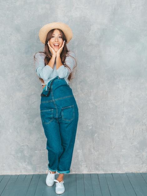 顔の近くの手で見ている若い美しい驚く女性。カジュアルな夏のオーバーオールの服と帽子でトレンディな女の子。スタジオで灰色の壁に近いポーズの女性 無料写真