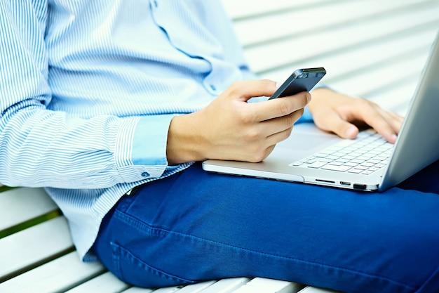 若い男がノートパソコンで作業、ノートパソコンの男の手、通りでカジュアルな服装のビジネス人 無料写真