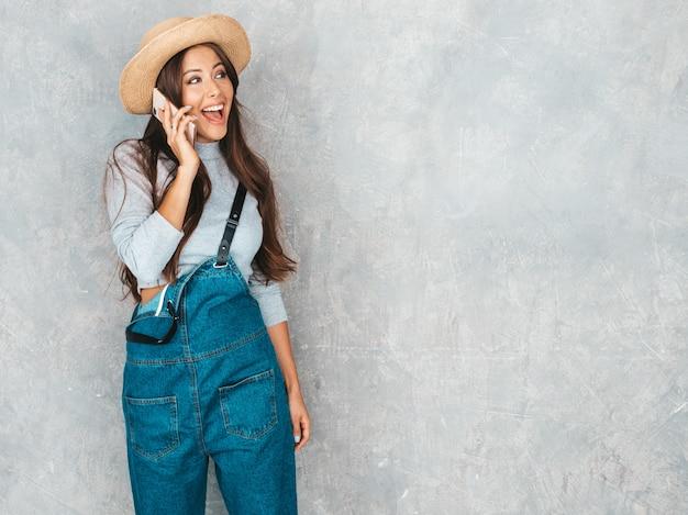 電話で話す若い美しい女性。カジュアルな夏のオーバーオールの服と帽子でトレンディな女の子。 無料写真