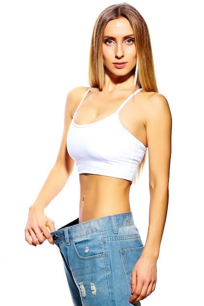 白で隔離され、大きなジーンズと美しい若い女性 無料写真