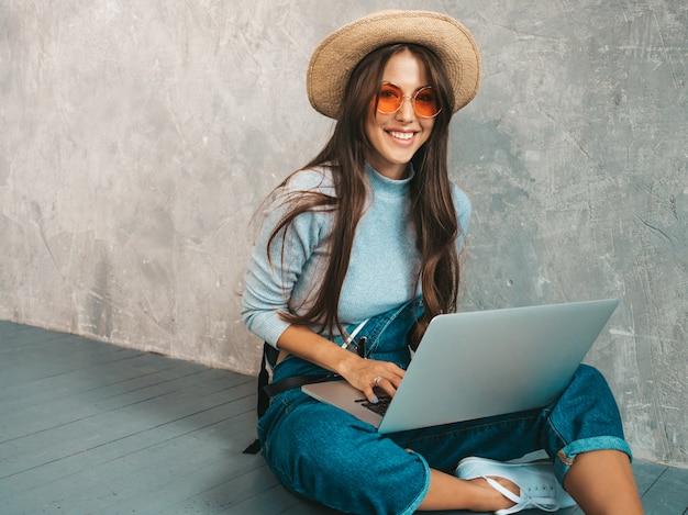 サングラスで創造的な若い笑顔の女性の肖像画。灰色の壁の近くの床に座って美しい少女。 無料写真