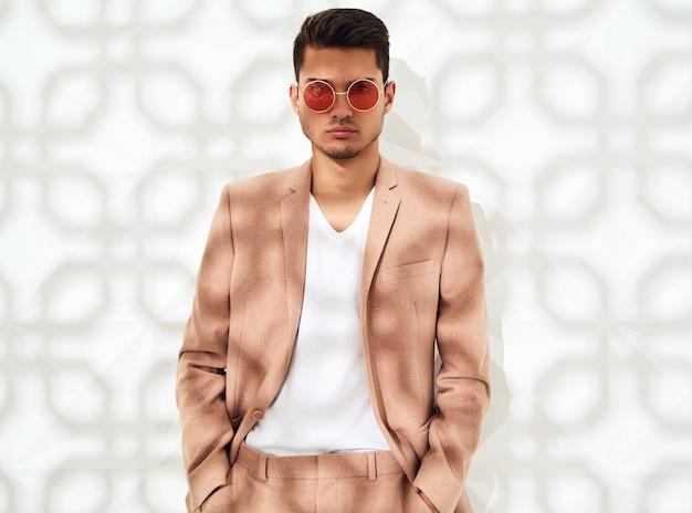 Модная стильная модель в элегантном светло-розовом костюме позирует возле белой стены Бесплатные Фотографии