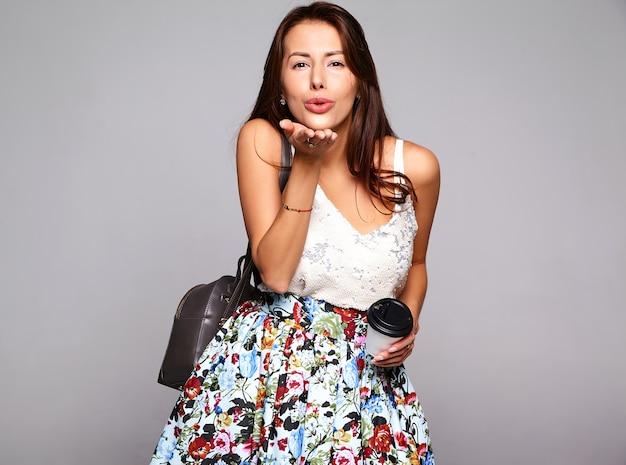 Модель женщины брюнет портрета красивая милая в вскользь одеждах лета без состава изолированного на сером цвете. поцелуй в воздухе и пить свежий кофе Бесплатные Фотографии