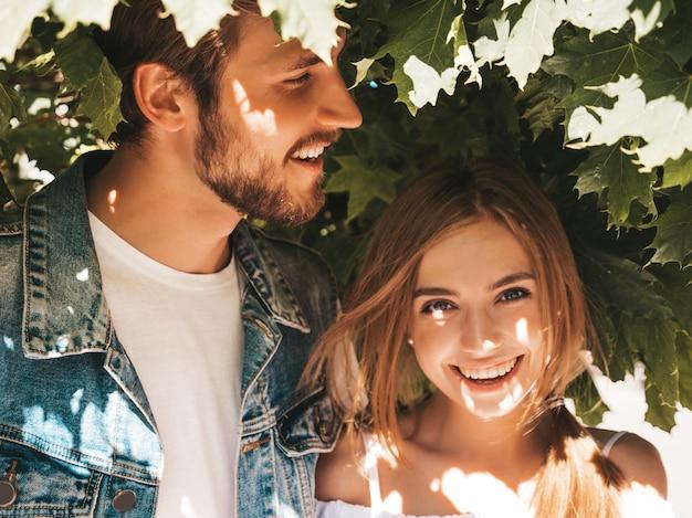 笑顔の美しい少女と彼女のハンサムなボーイフレンドは木の近くの通りでポーズします。 無料写真
