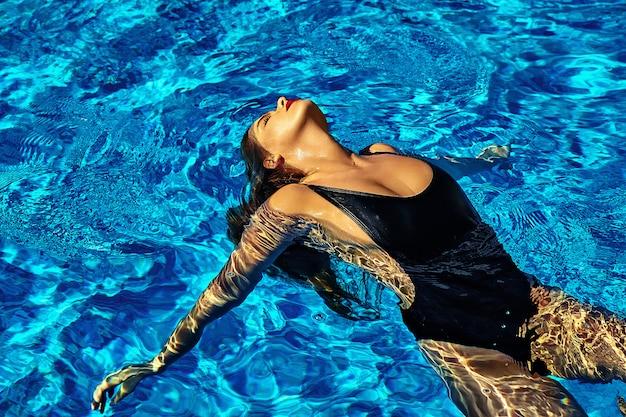 赤い唇とスイミングプールで背中に泳ぐ黒い水着で黒い髪とセクシーなホット美少女モデルのファッション写真 無料写真