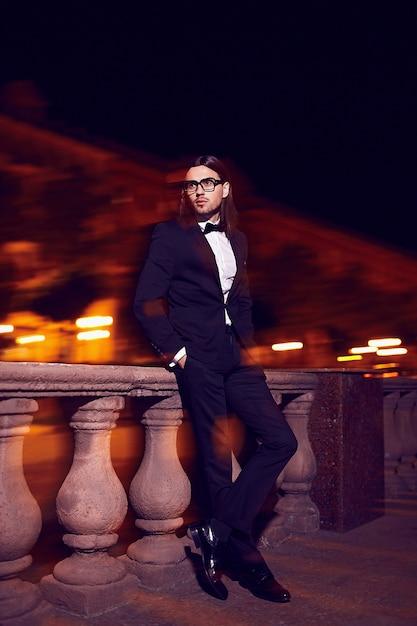 Портрет моды элегантный длинноволосый молодой человек. привлекательная и красивая мужская модель в черном костюме с усами на улице ночью Бесплатные Фотографии