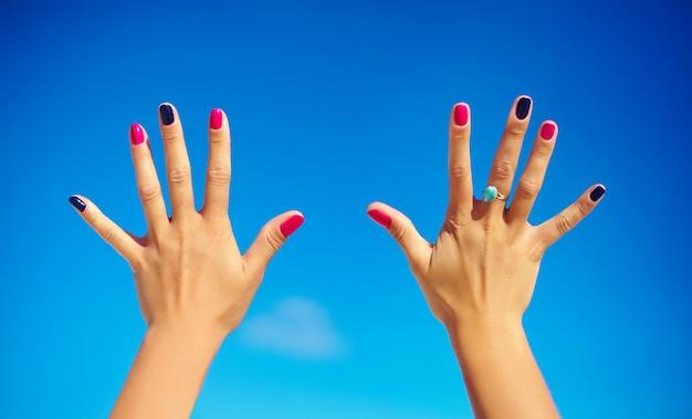 Человеческие руки с яркими красочными гвоздями над голубым небом Бесплатные Фотографии