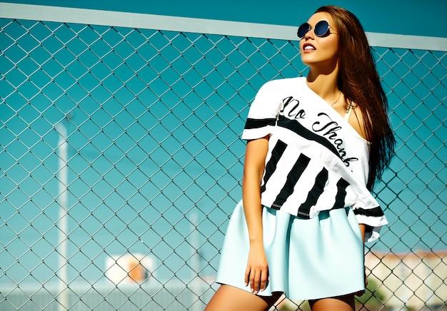 面白いクレイジーグラマースタイリッシュなセクシーな笑みを浮かべて美しい若い女性モデルの明るいヒップスター夏のカジュアルな服装で青い空の後ろの通り 無料写真