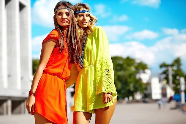 Фасонируйте портрет молодых моделей хиппи женщин в солнечный летний день в яркой красочной одежде битник Бесплатные Фотографии