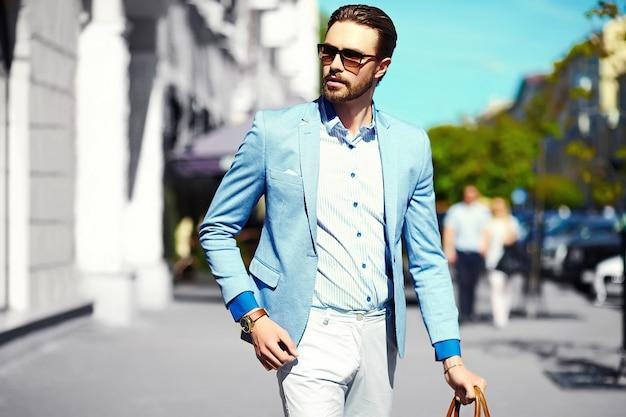 ファッション性の高い外観。サングラスで通りのスーツ布ライフスタイルで若いスタイリッシュな自信を持って幸せなハンサムな実業家モデル 無料写真