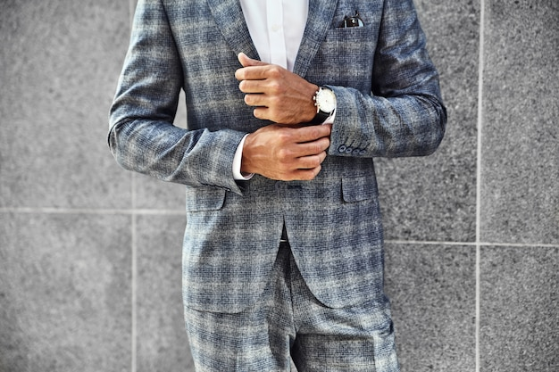 Модель бизнесмена моды одела в элегантном изменчивом костюме, позирующем около серой стены на фоне улицы. метросексуал с роскошными часами на запястье Бесплатные Фотографии