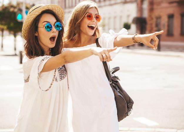 Две модные молодые стильные хиппи брюнетка и блондинка модели женщин в солнечный летний день в белых одеждах битник позирует. указывая на продажи магазина Бесплатные Фотографии