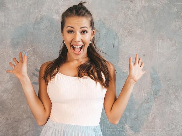 空気中の手で見ている若い美しい驚く女性。カジュアルな夏服でトレンディな女の子。灰色の壁に近いポーズの女性 無料写真