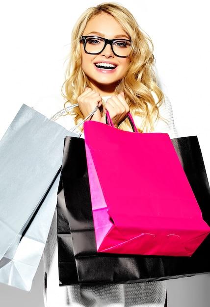 Портрет красивые милые счастливые сладкие улыбающиеся блондинка женщина держит в руках большие покупки красочные сумки в хипстерской одежде, изолированных на белом Бесплатные Фотографии