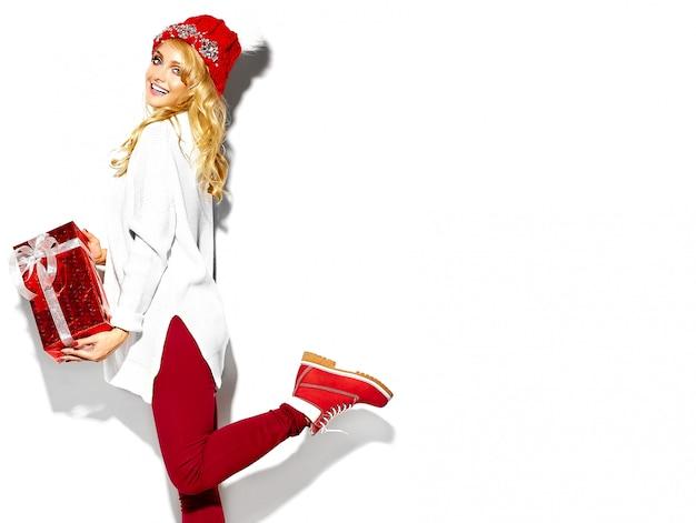 Портрет красивой счастливой сладкой улыбающейся блондинки, держащей в руках большую рождественскую подарочную коробку в повседневной красной хипстерской зимней одежде, в белом теплом свитере, стоящем на одной ноге Бесплатные Фотографии