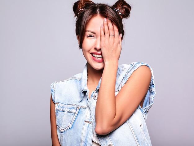 グレーに分離された角の髪型と化粧なしでカジュアルな夏ジーンズ服で美しいかわいいブルネットの女性モデルの肖像画。彼女の顔を手で覆う 無料写真
