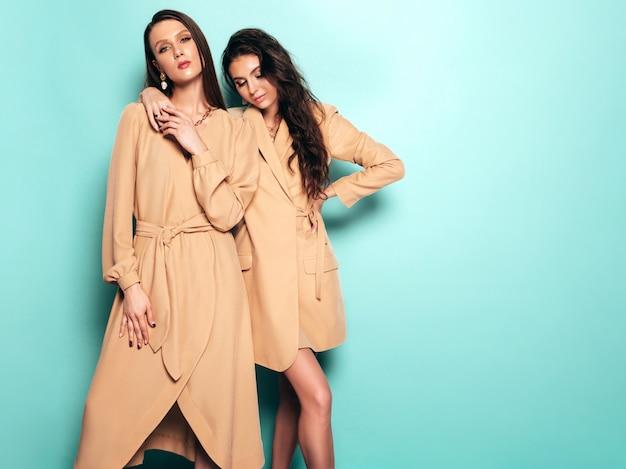 Две молодые красивые брюнетки девушки в красивых модных летних костюмах одинаковых костюмов. сексуальные беззаботные женщины позируют возле синей стены в студии Бесплатные Фотографии