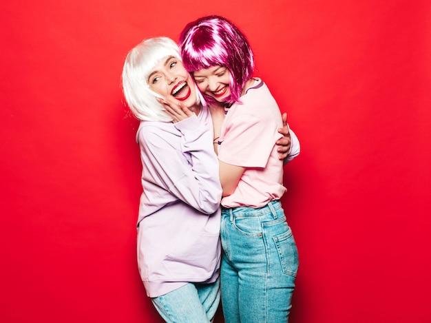Две молодые сексуальные улыбающиеся хипстерские девушки в белых париках и красных губах. красивые модные женщины в летней одежде. беззаботные модели позируют возле красной стены в студии, сходя с ума Бесплатные Фотографии