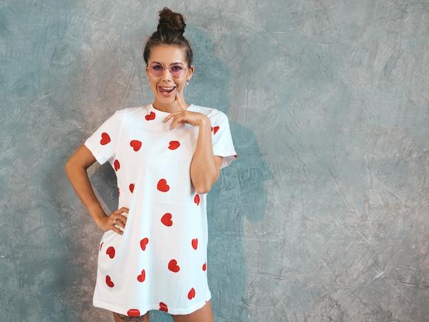 探している若い美しい笑顔の女性。カジュアルな夏の白いドレスとサングラスでトレンディな女の子。 無料写真