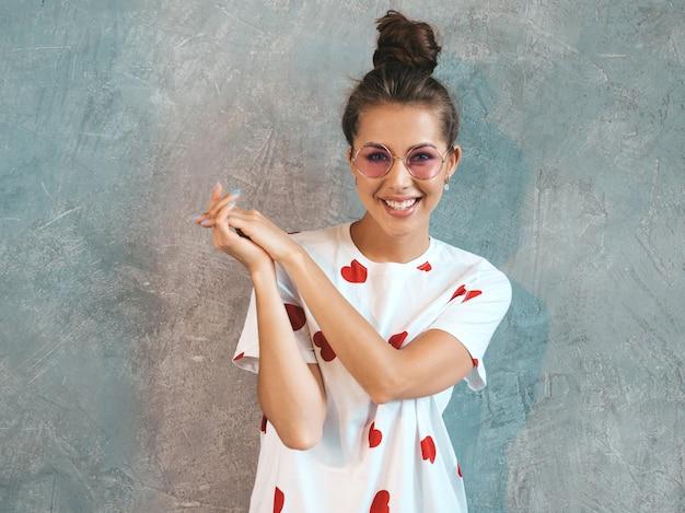 Портрет молодой красивой улыбается женщина ищет. модные девушки в случайные летнее белое платье и солнцезащитные очки. Бесплатные Фотографии