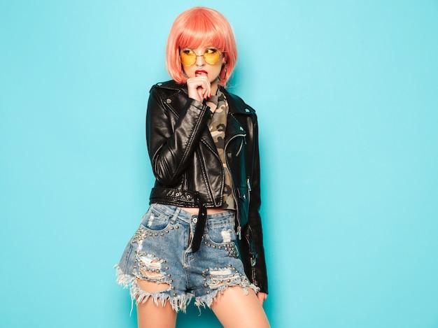 Плохая девушка молодой красивый битник в черной кожаной куртке и серьги в носу. сексуальная беззаботная женщина позирует в студии в розовом парике возле синей стены. уверенно модель в солнцезащитные очки. Бесплатные Фотографии