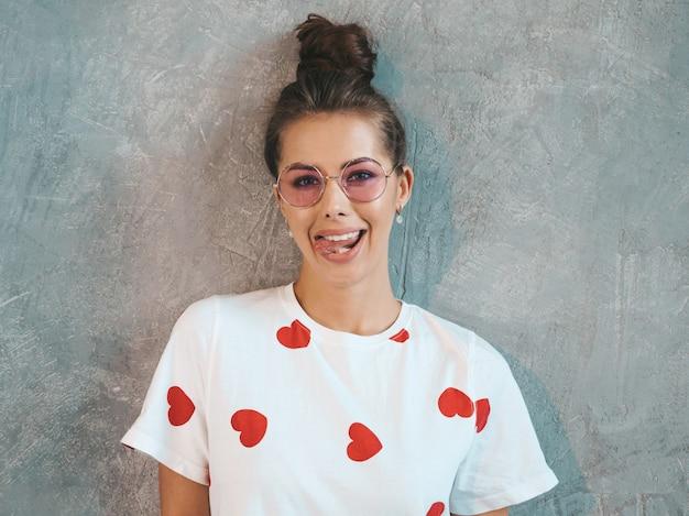探している若い美しい笑顔の女性。カジュアルな夏の白いドレスとサングラスでトレンディな女の子。 。舌を見せて 無料写真