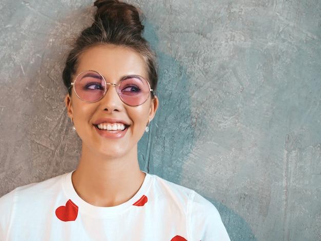 探している若い美しい笑顔の女性のクローズアップの肖像画。カジュアルな夏の白いドレスとサングラスでトレンディな女の子。 無料写真