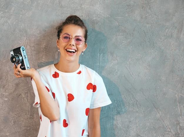 Красивая молодая девушка улыбается фотограф фотографировать, используя ее ретро камеры. Бесплатные Фотографии