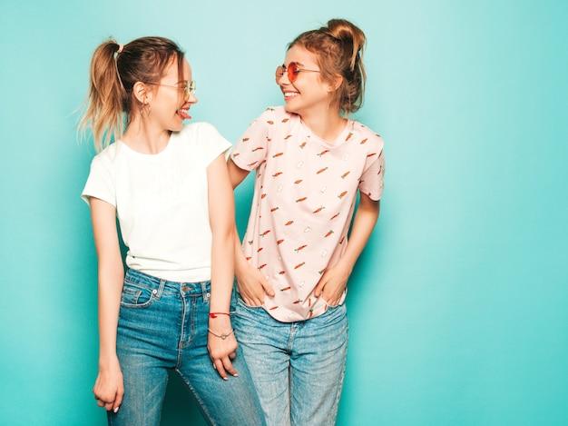 Две молодые красивые белокурые улыбающиеся хипстерские девочки в модных летних хипстерских джинсовых одеждах. сексуальные беззаботные женщины позируют возле синей стены. модные и позитивные модели с удовольствием в солнцезащитных очках Бесплатные Фотографии